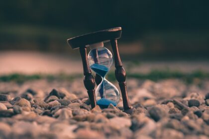 An image of a small hourglass on a ground covered with pebbles.