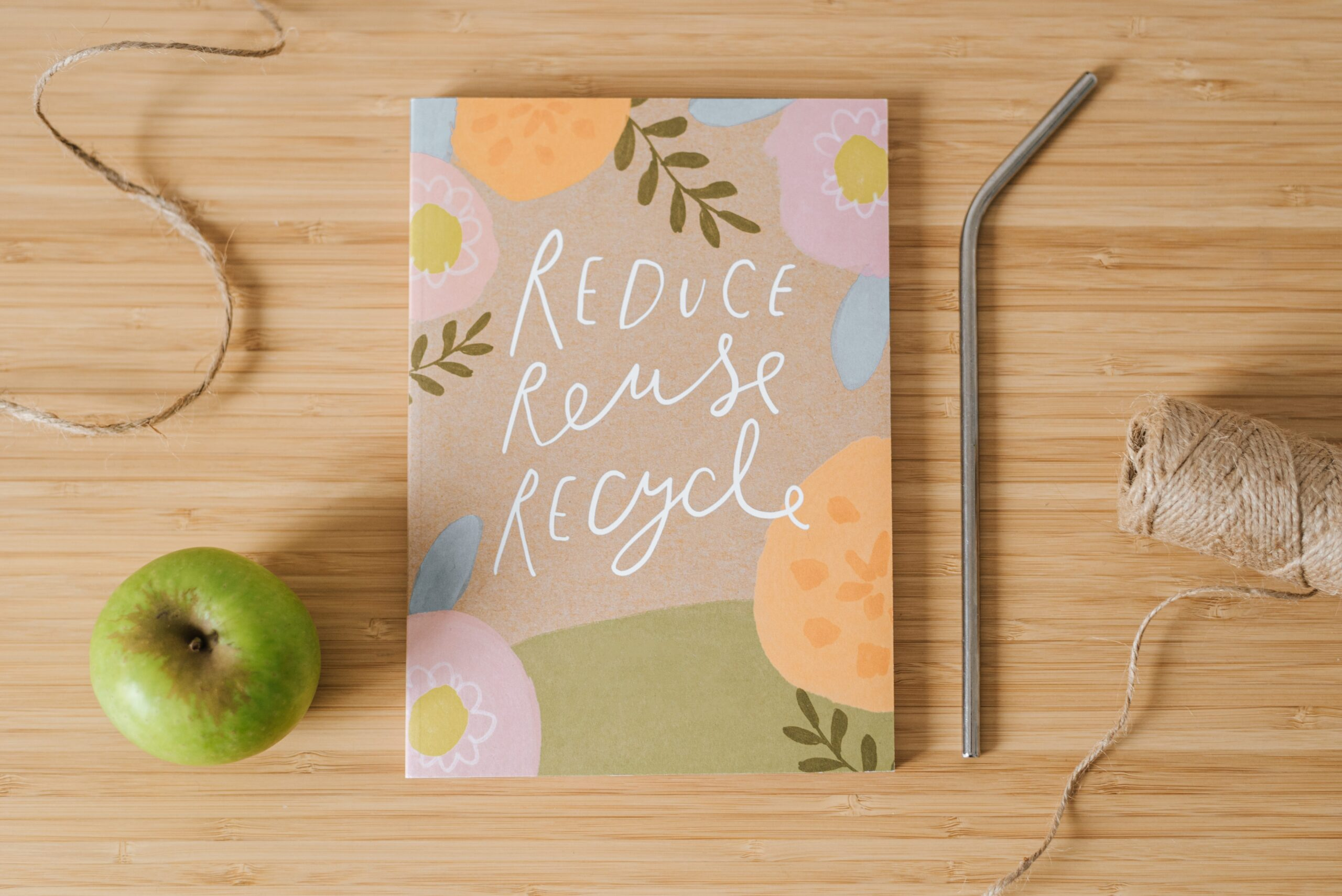 """Notebook that has, """"Reduce, Reuse, Recycle"""" written on the cover is placed on a desk and has an apple, a metal straw, and string next to it."""