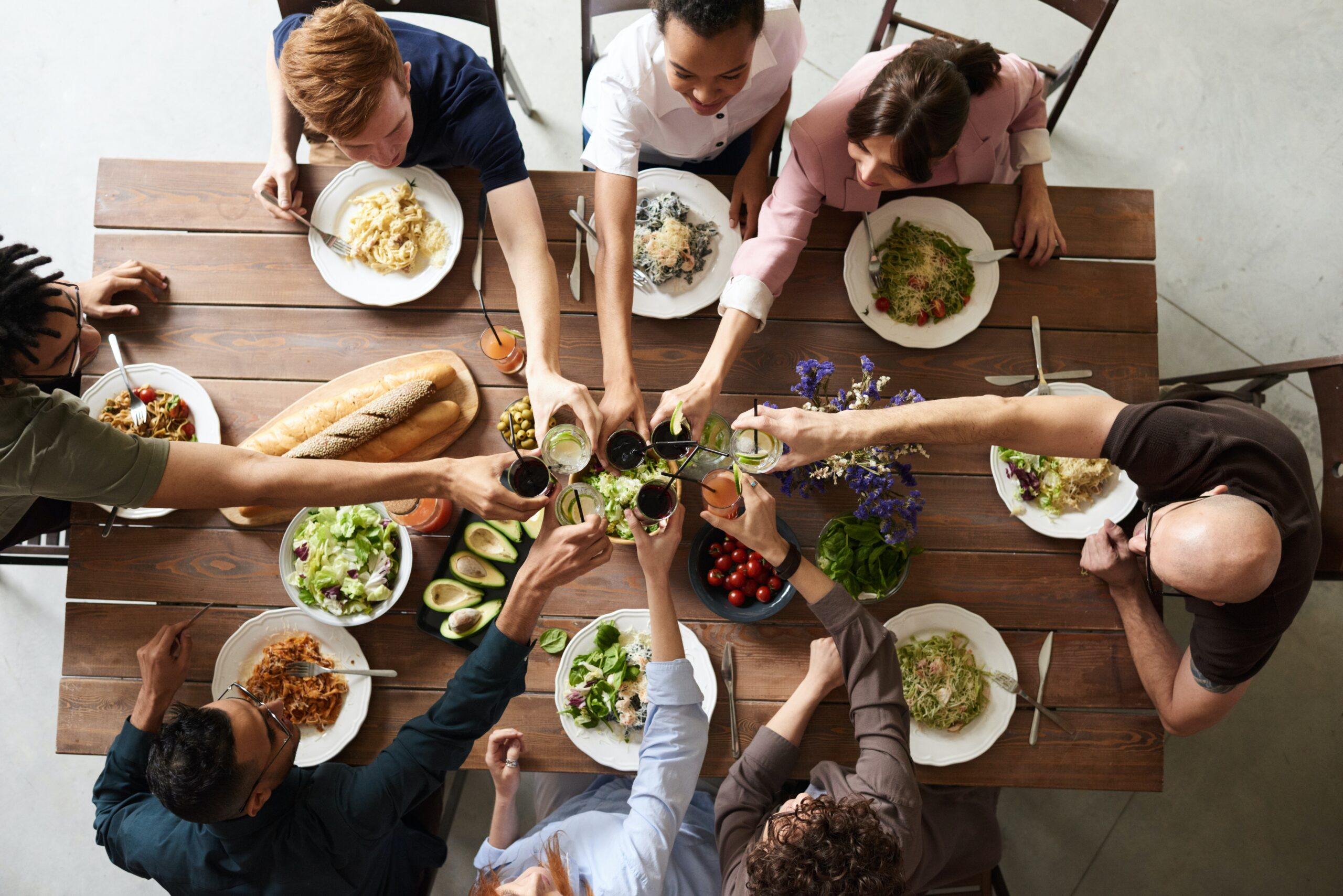 A group of people having a meal together as they raise a toast.