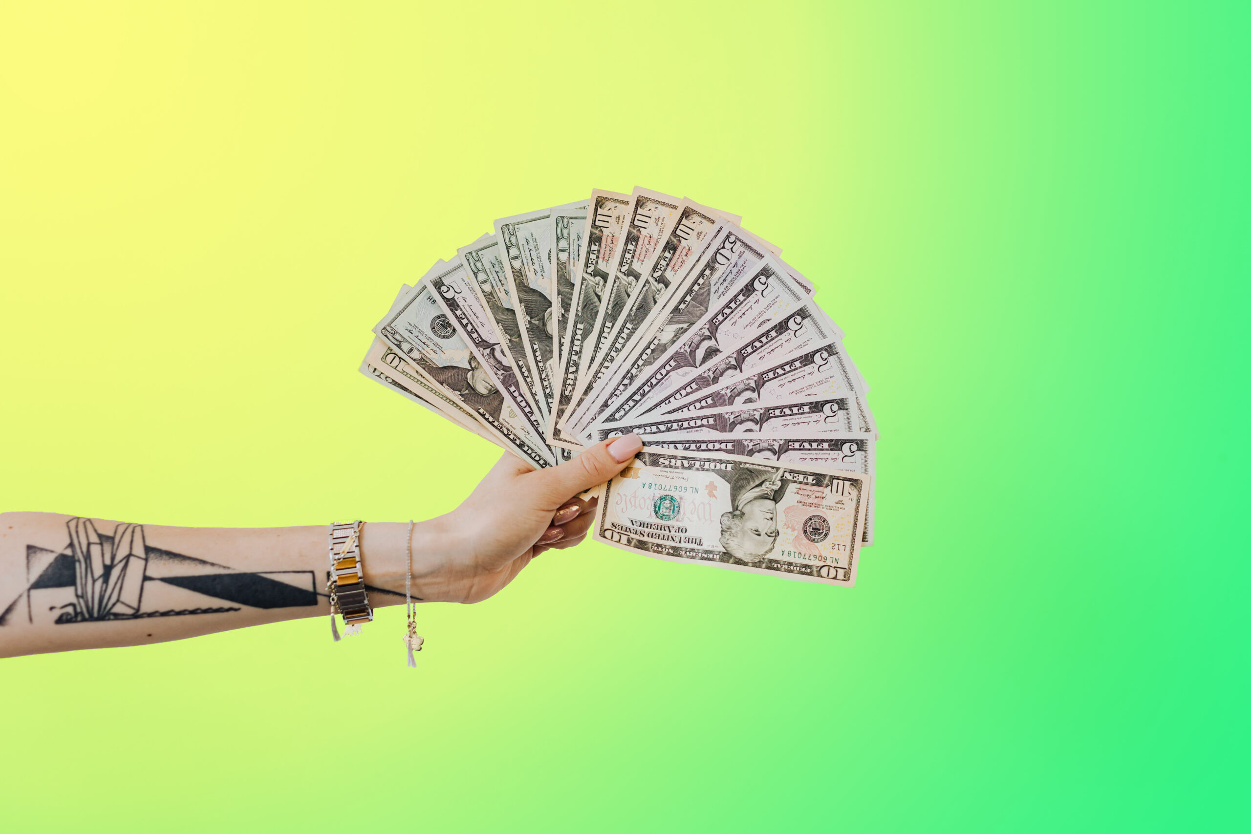 An outstretched arm with a tattoo on it is holding several 5, 10, and 20 dollar bills in a fan formation.